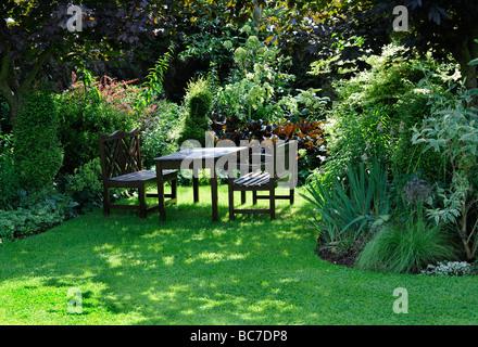 Tavolo e sedie in un paesaggistico giardino inglese in Stoberry Park, Somerset, Regno Unito Foto Stock