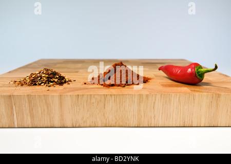 Selezione dei tipi di peperoncini secchi, polverizzato e fresche, sul tagliere di legno Foto Stock