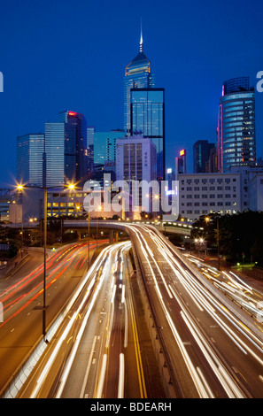 Un edificio alto e sentieri per auto a notte nel centro di Hong Kong, Cina. Foto Stock