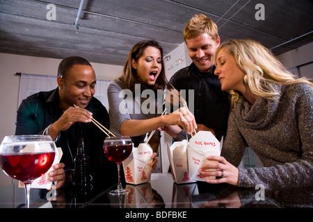 Multi-etnico coppie di mangiare il cinese take-out nei moderni loft Foto Stock