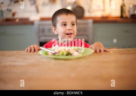 Ragazzo seduto a tavola non mangiare un piatto di cibo Foto Stock