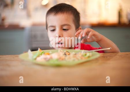 3 anno vecchio ragazzo di mangiare il cibo con le mani da una piastra Foto Stock
