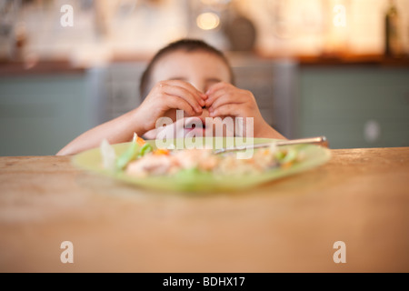 3 anno vecchio ragazzo siede ignorando il suo cibo al tavolo per la cena Foto Stock