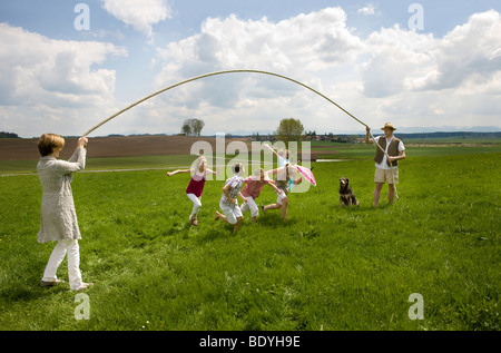 La famiglia felice jump roping in campagna Foto Stock