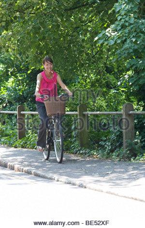 Una giovane donna in bicicletta lungo una strada di campagna Foto Stock