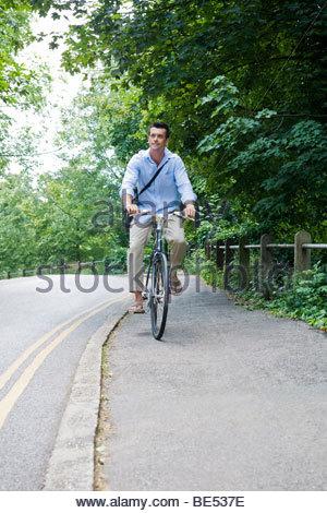 Un uomo in bicicletta lungo una strada di campagna Foto Stock