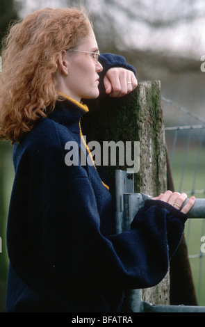 Donna appoggiato su di una recinzione, uno solo Foto Stock