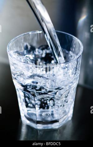 Close-up di acqua versata in un bicchiere Foto Stock