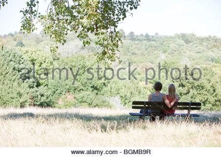 Una giovane coppia seduta su una panchina nel parco Foto Stock