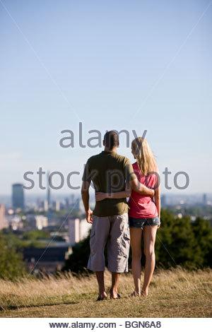 Una giovane coppia in un parco, guardando attraverso la città Foto Stock