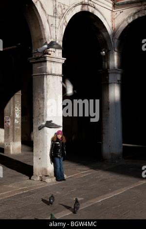Bambina guarda piccioni in un luogo veneziano a SOTOPORTEGO DEL BANCOGIRO, RIALTO MERCATO VENEZIA, Italia Foto Stock
