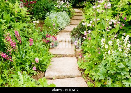 Percorso della pavimentazione in lastre estivo tra confini di aquilegia fiori in un paese di lingua inglese giardino Foto Stock