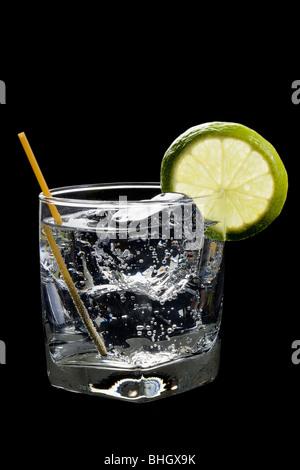 Club soda o gin o vodka e tonico con calce fetta guarnire su sfondo nero Foto Stock