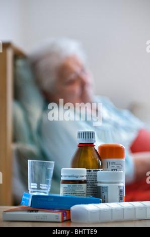 Signora anziana in appoggio a letto nella sua camera con una varietà di farmaci e distributori in primo piano Foto Stock