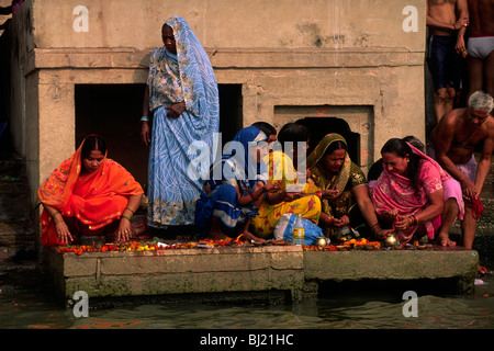 India, Varanasi, fiume Gange, donne dando offerte a ALBA Foto Stock