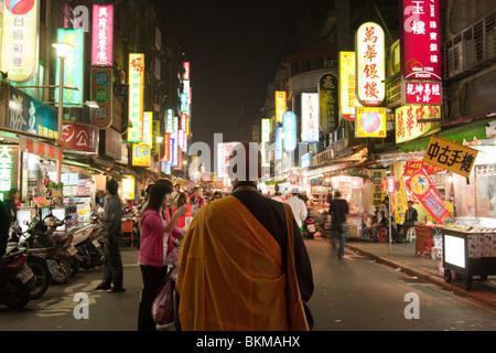 La gente a piedi passato un monaco, la strada affollata scena mostrando illuminazione infinita di cartelloni e people Foto Stock