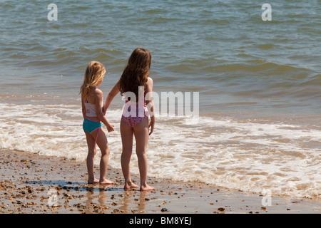 Due giovani ragazze in abiti nuotare assieme a bordo di mare sulla spiaggia affacciata sul mare Foto Stock
