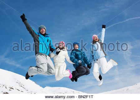 Famiglia jumping in mid-aria nella neve Foto Stock