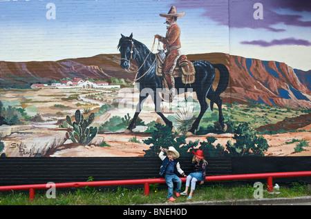 I bambini di fronte a un muro dipinto in Stockyards, Fort Worth, Texas, Stati Uniti d'America Foto Stock