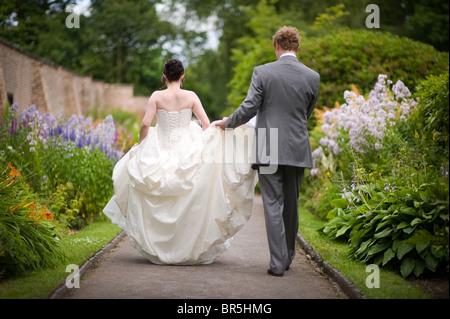 Sposa e lo sposo a passeggio tra aiuole - lo sposo tenendo il treno del vestito Foto Stock