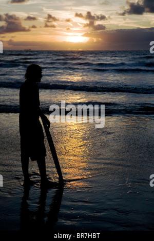 Ragazzo guardare il sole che tramonta sulla costa olandese Foto Stock
