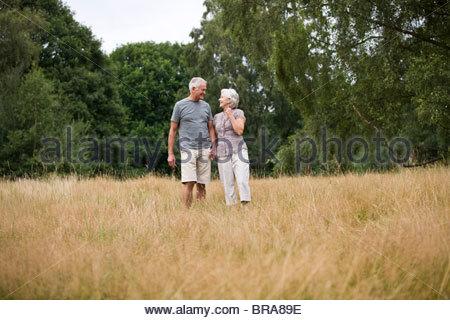 Una coppia senior in piedi in un campo, tenendo le mani Foto Stock