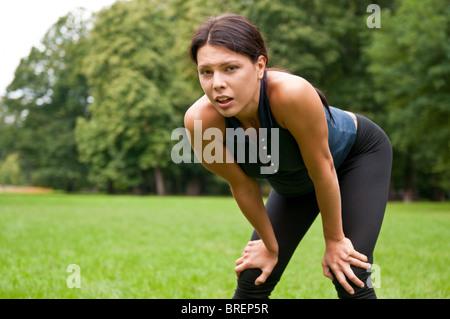 Giovane donna con pausa dopo il jogging nel parco - appoggiata contro le ginocchia Foto Stock