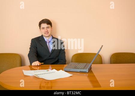 L imprenditore si siede a un tavolo con il computer portatile Foto Stock