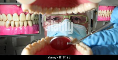 Un dentista lavorando sul modello denti con tv visualizza di teeeth in background Foto Stock