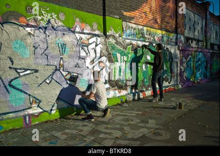 Due graffiti artisti che operano su un pezzo a Monaco di Baviera, Germania Foto Stock