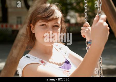 Giovane ragazza seduta su un altalena in un parco Foto Stock