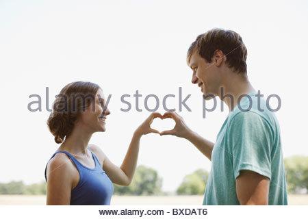 Coppia sorridente usando le mani per prendere forma di cuore Foto Stock