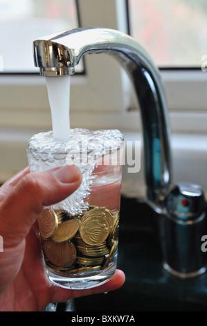 Foto concettuale di un rubinetto di riempimento in vetro pieno di monete d oro con acqua che illustra lo spreco Foto Stock