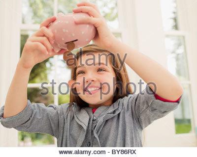Eccitato ragazza lo svuotamento delle monete dal salvadanaio Foto Stock