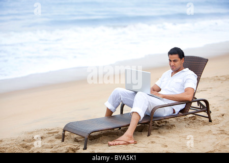 L'uomo con un laptop a una spiaggia Foto Stock