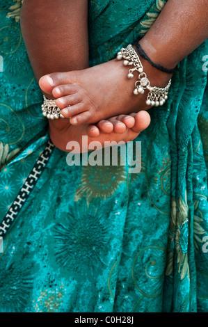 Bambini indiani a piedi nudi contro le madri floreale verde sari. Andhra Pradesh, India Foto Stock