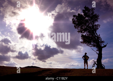 Ciclista stand sulla collina a guardare la luce del sole e relax Foto Stock