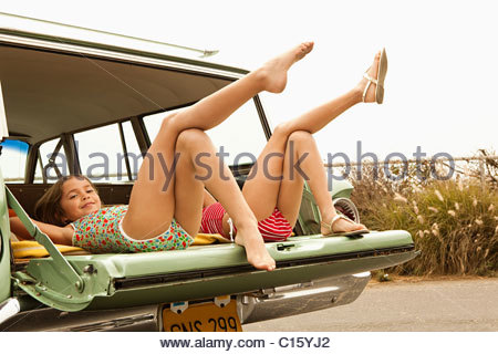 Due ragazze che giace nella station wagon con gambe in aria Foto Stock