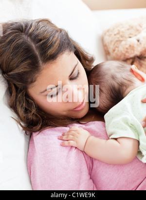 Ritratto di un bambino e sua madre dorme tranquillamente in poltrona a casa Foto Stock