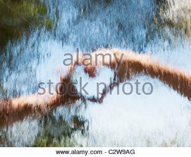 Mani rendendo cuore-forma dietro il vetro Foto Stock