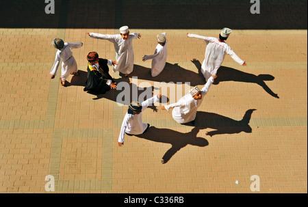 Oman, Moscato, vista dall'alto di ragazzi della scuola in piedi con le braccia e ballare sul terreno in una giornata Foto Stock