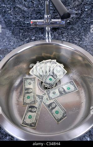 Dollari USA in un lavandino con scarico acqua in concetto i buoni soldi andando giù il drain. Foto Stock