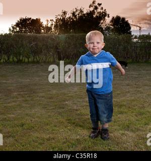 Giovane ragazzo giocando al di fuori Foto Stock
