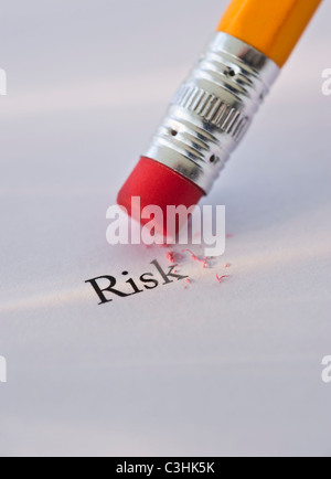 Studio shot di matita di cancellare la parola rischio dal pezzo di carta Foto Stock