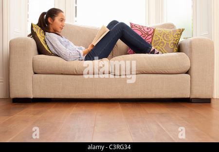 Ragazza adolescente lettura sul divano Foto Stock