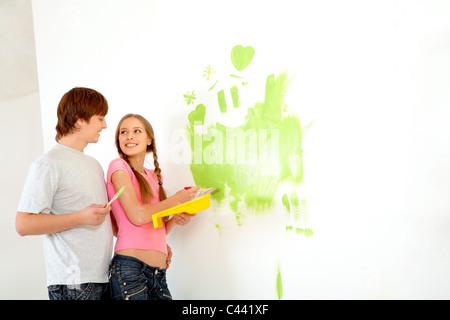 Giovane coppia felice pittura pareti nella nuova casa Foto Stock