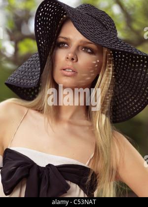 Ritratto di una giovane e bella donna che indossa un cappello per il sole Foto Stock