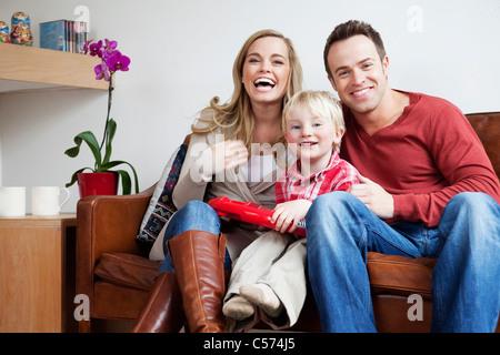 Famiglia seduti sul divano insieme Foto Stock