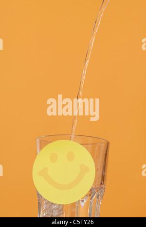 L'acqua versata nel bicchiere, Smiley in primo piano Foto Stock