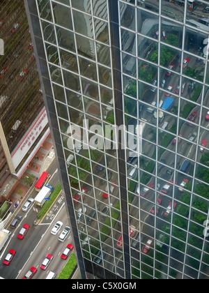 Vista guardando verso il basso sulle strade di Hong Kong di seguito riflessa nelle finestre di vetro dell'immigrazione Foto Stock